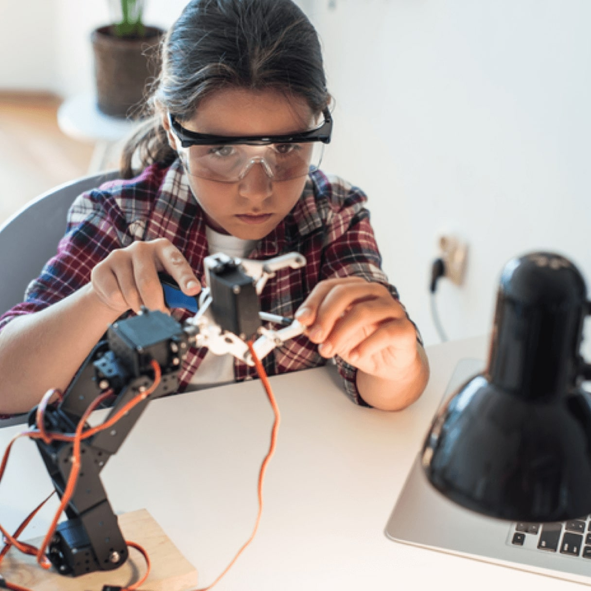 A student builds a robot while video chatting with a teacher and receiving personalized instructions.