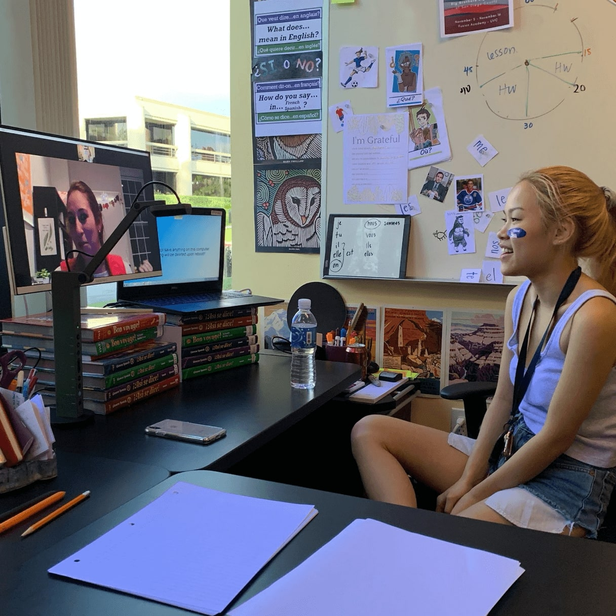 Student and teacher video chat while student works on course work at their desk at home.
